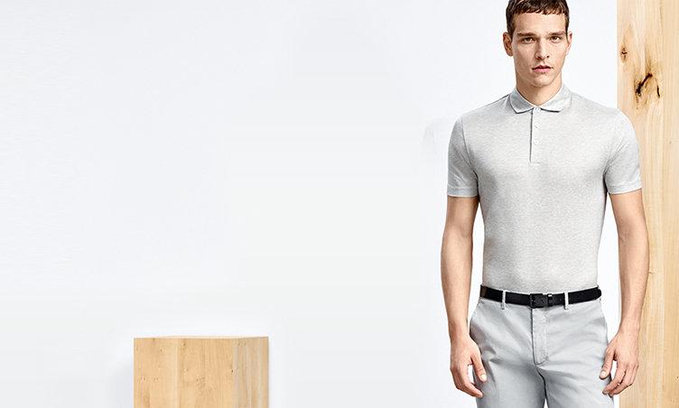 Models aus verschiedenen Perspektiven mit grauen und grau-weiß gestreiften Poloshirts, grauen Hosen und schwarzen Gürteln.