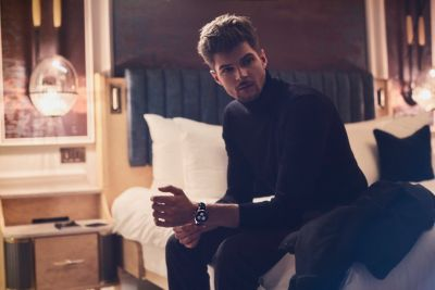 Jim Chapman indossa un maglione con colletto a tartaruga e l'orologio Companion nero by BOSS.
