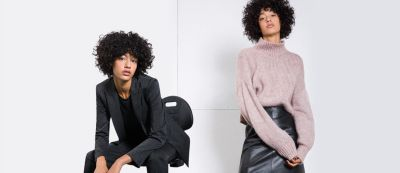Vrouwelijke modellen dragen een zwart broekpak en een roze trui met een zwarte leren rok van HUGO Womenswear