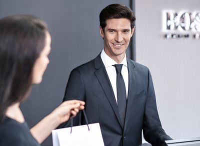 Homme en costume gris faisant du shopping dans une boutique BOSS