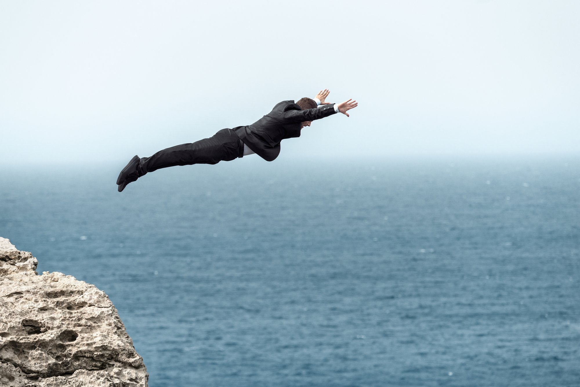Klifduiker David Colturi springt van een klif terwijl hij het Superblack-kostuum van HUGO draagt