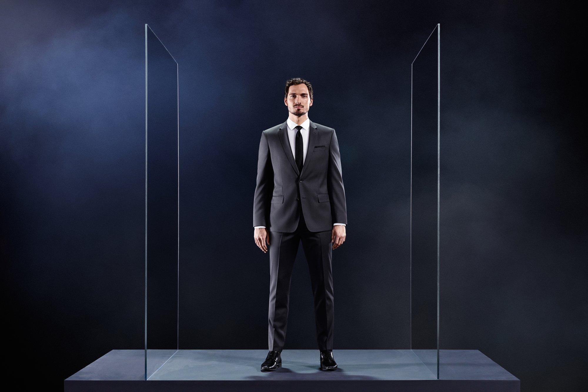 Mats Hummels in einem grauen Anzug, einem weißen Hemd und einer schwarzen Krawatte von BOSS