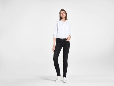 Female model wearing black jeans and white shirt by BOSS
