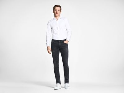 Male model wearing black jeans and white shirt by BOSS