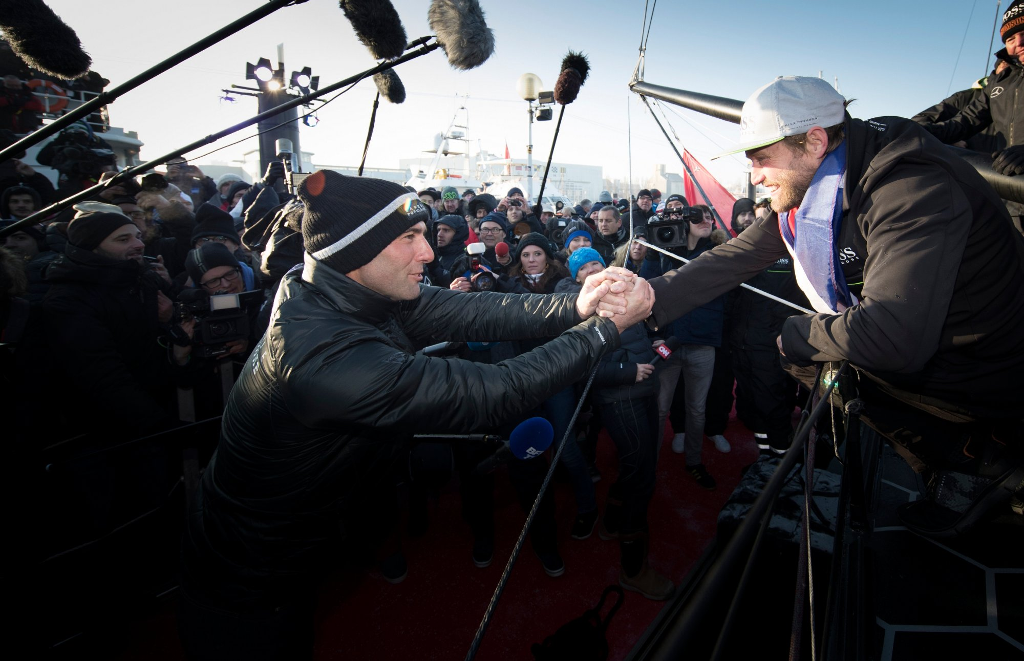 Alex Thomson greeting a fan while standin on top of the HUGO BOSS yacht