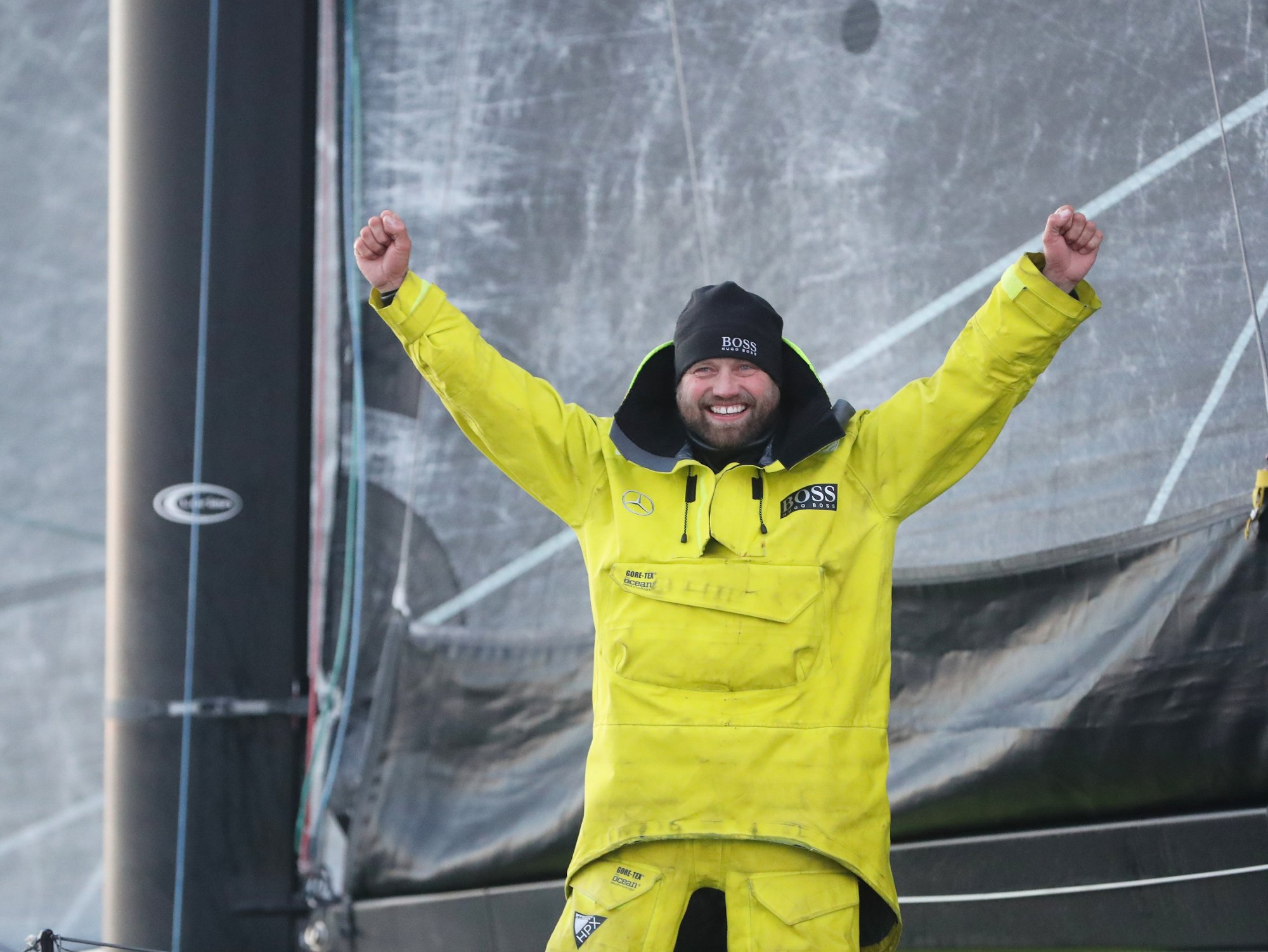 Alex Thomson wearing a yellow sailing jacket by BOSS