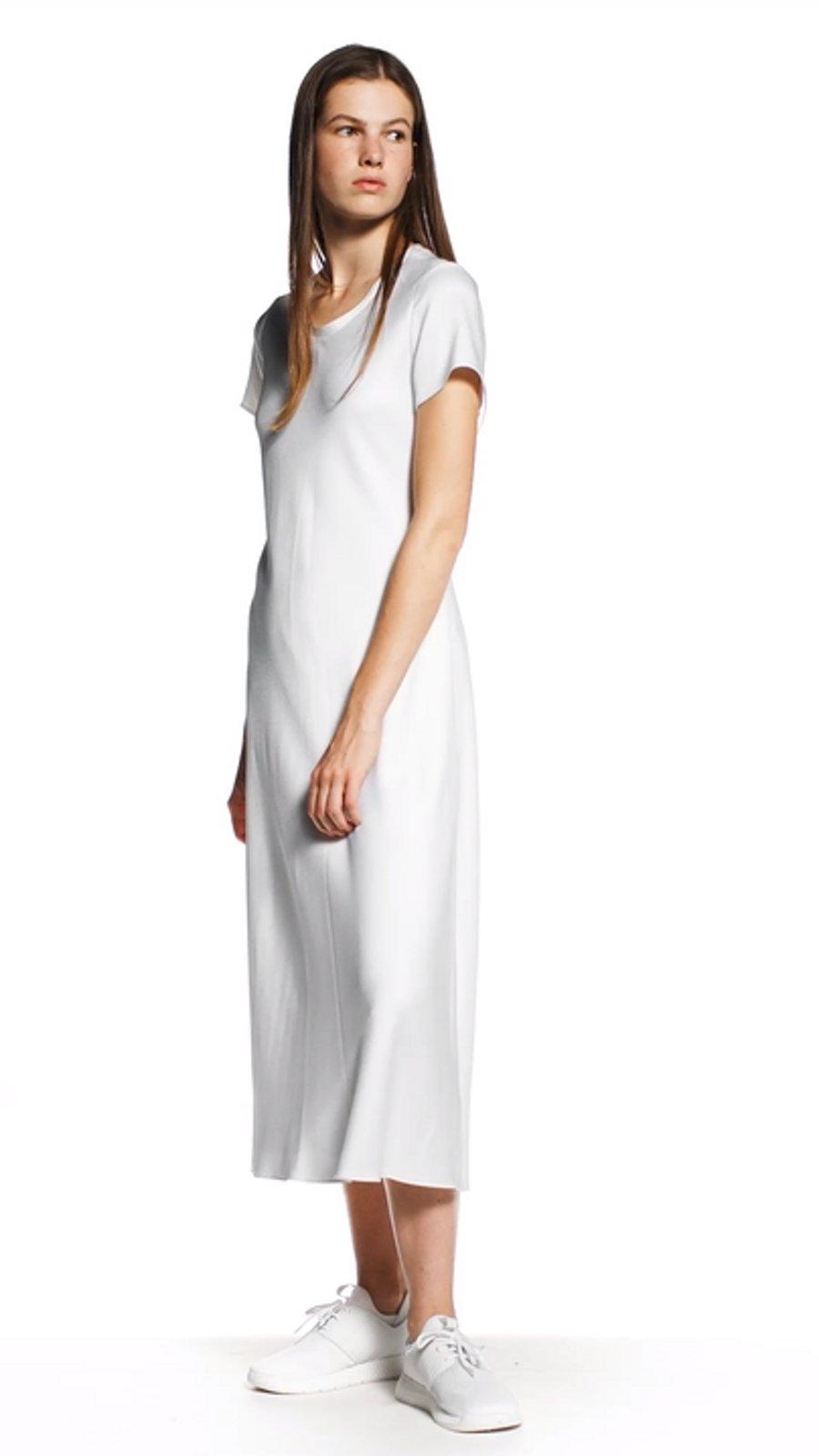 ab1fc7659da1 La donna indossa un vestito bianco e scarpe bianche BOSS ...