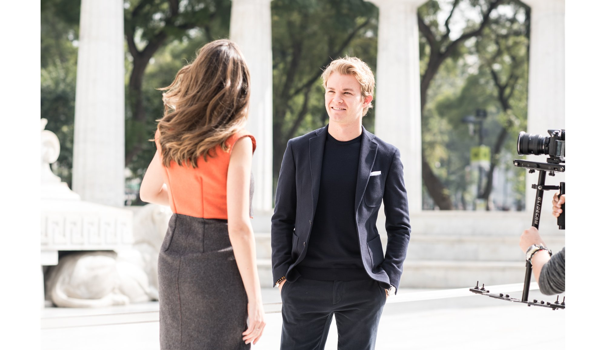 Nico Rosberg wearing a black shirt and suit by BOSS, Lety Sahagún wearing a gray skirt and orange top by BOSS
