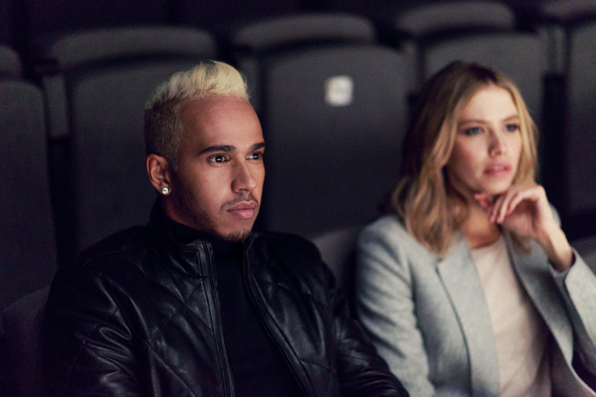 Lewis Hamilton wearing a black shirt and leather jacket by BOSS, Lena Perminova wearing a white shirt and gray blazer by BOSS