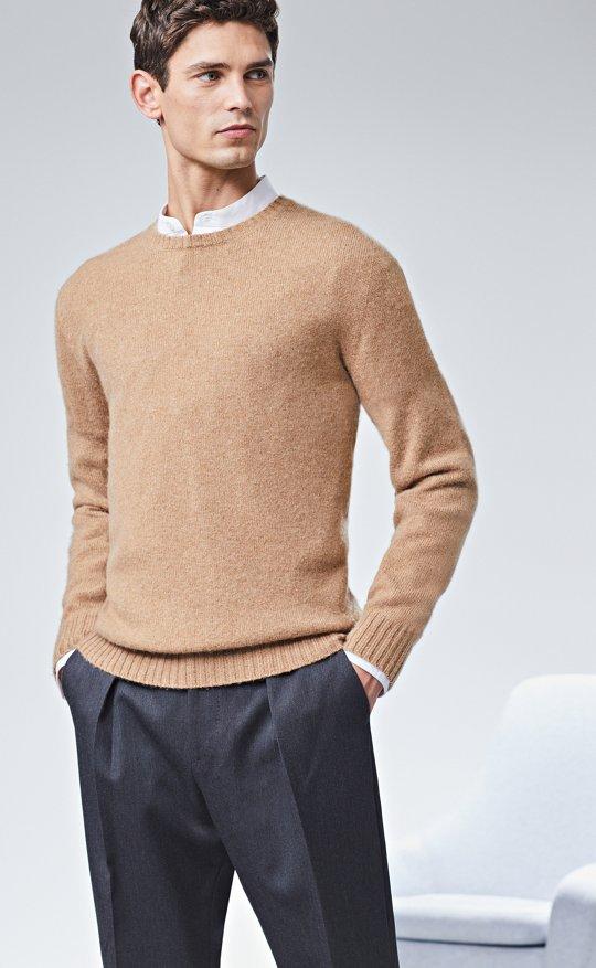 Le mannequin porte une chemise, un pull beige et un pantalon ... 1be11298e926