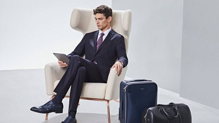 Man is wearing a suit by BOSS alongside a suitcase