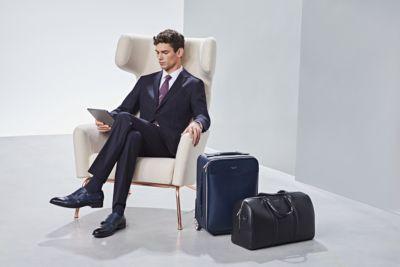 Man draagt een kostuum van BOSS met een koffer
