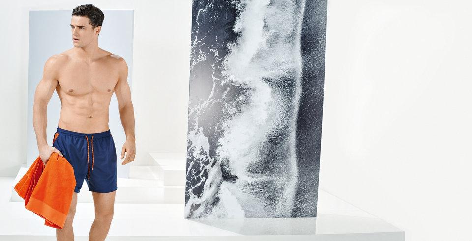 Model met grijze zwemshort van HUGO BOSS en een licht windjack.