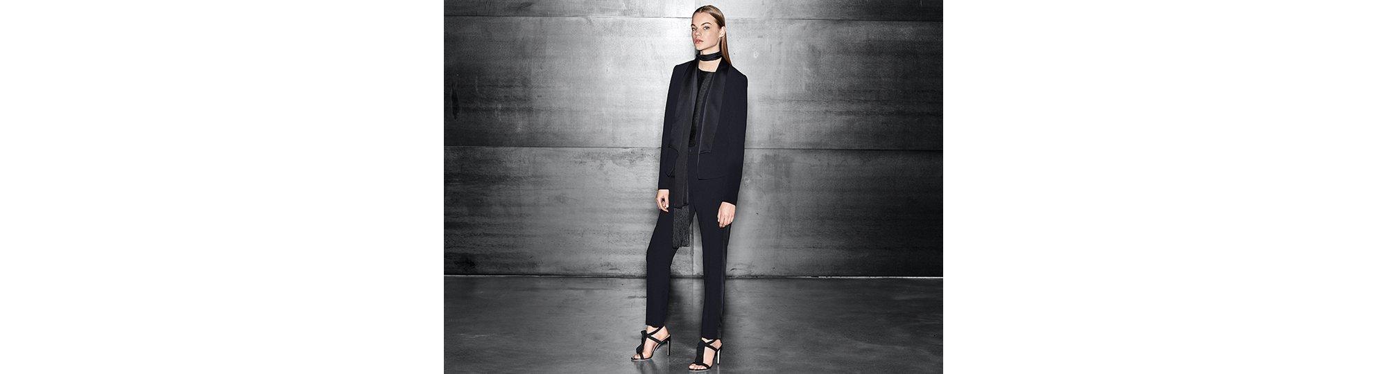 Vrouw draagt womenswear-smoking met zwarte hoge hakken van BOSS