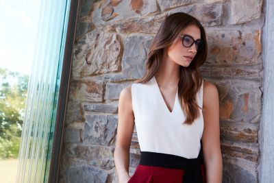 Rianne Van Rompaey mit einer braunen Sonnenbrille und einem schwarzen Kleid von BOSS