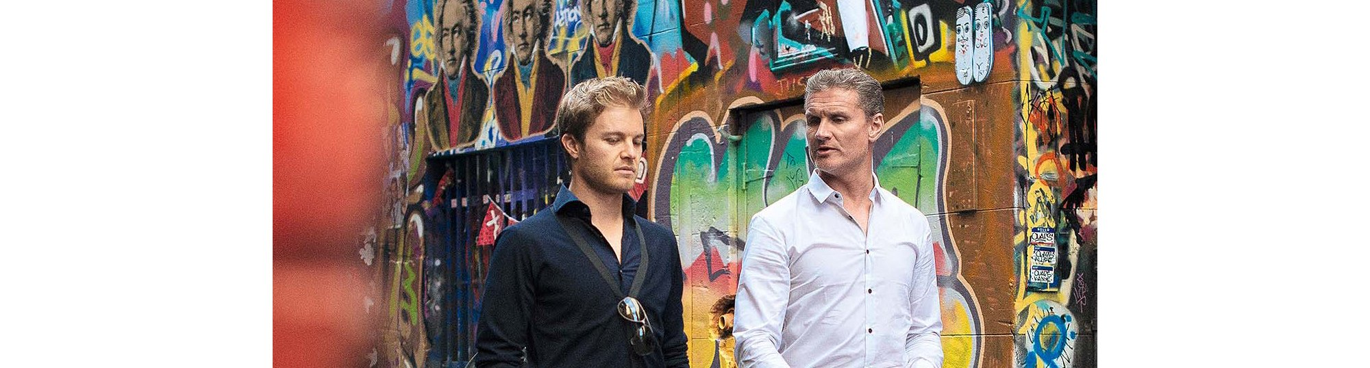 Nico Rosberg wearing a dark blue shirt and sunglasses by BOSS, David Coulthard wearing a white shirt by BOSS