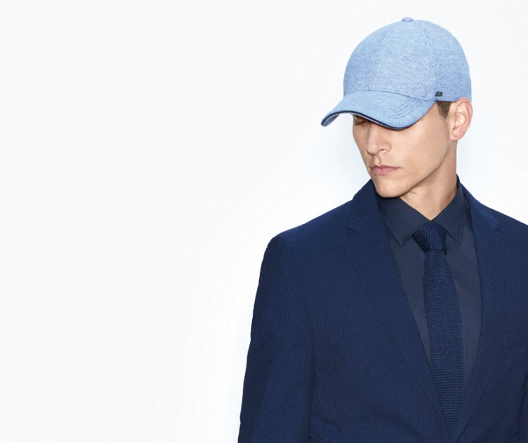 Model mit sportlichem HUGO BOSS Baseball Cap. Mit hellblauen Farbakzenten. Kombiniert mit dunkelblauem Anzug.