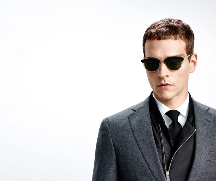 Model with modern HUGO BOSS sunglasses.  Spectacle frame out of black plastic and gold-coloured metal.