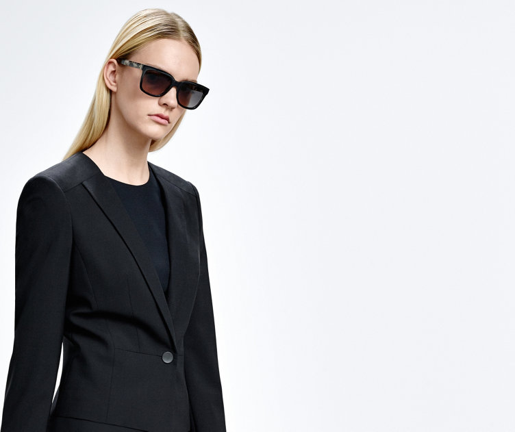 Model with HUGO BOSS sunglasses. Bold design with dark frame and light details.