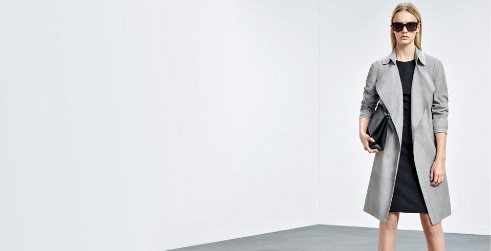 Model in grauem BOSS Trenchcoat aus Lammleder. Kombiniert mit schwarzem Kleid, schwarzer Handtasche und dunkler Sonnenbrille.