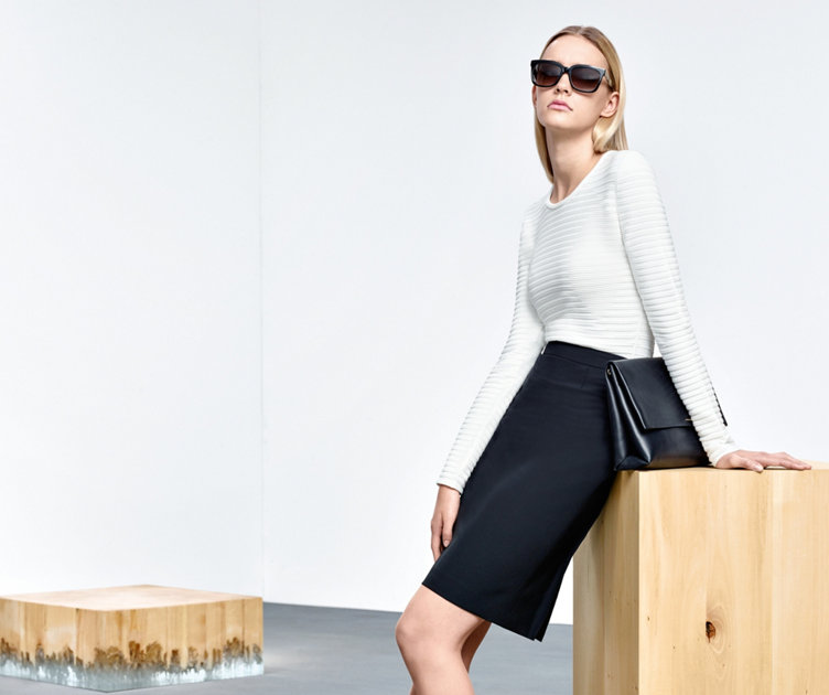 Model with elegant HUGO BOSS peplum pullover in white.  Fitted. Combined with black pencil skirt and handbag.