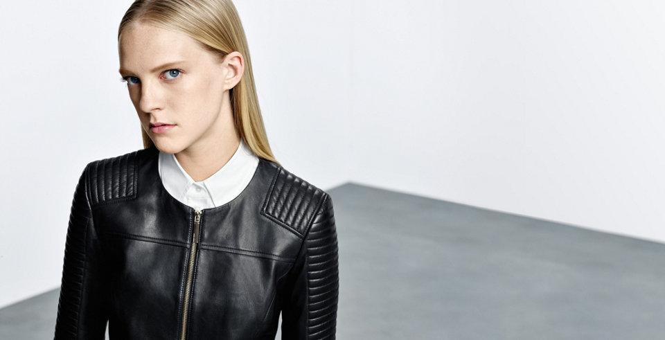 Model met zwarte leren jas van HUGO BOSS van glad lamsleer met stiksels bovenop de schouders.