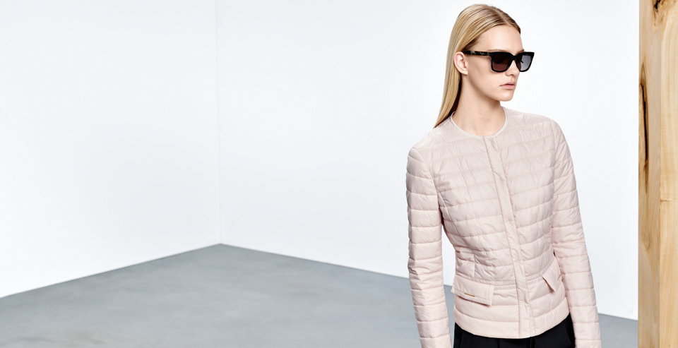 Model with a light quilted HUGO BOSS jacket in rose. Tailored and waisted cut. Combined with dark sunglasses.
