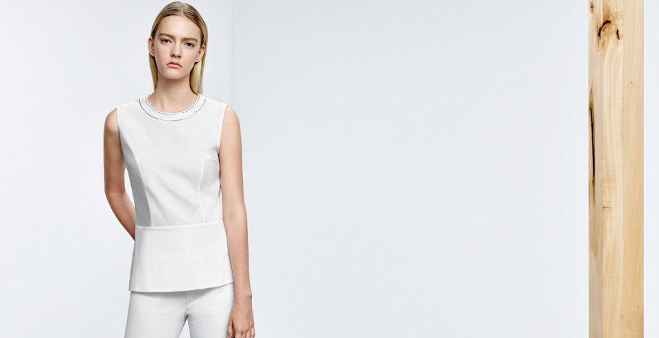 Model in weißem BOSS Top. Mit Besatz amAusschnitt, Abnähern und leicht ausgestelltem Schnitt.