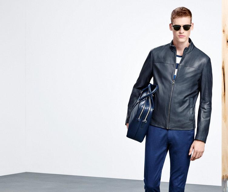 Le mannequin porte un blouson en cuir noir confectionné en cuir souple, un pantalon bleu, un sac en cuir bleu et des lunettes de soleil modernes.