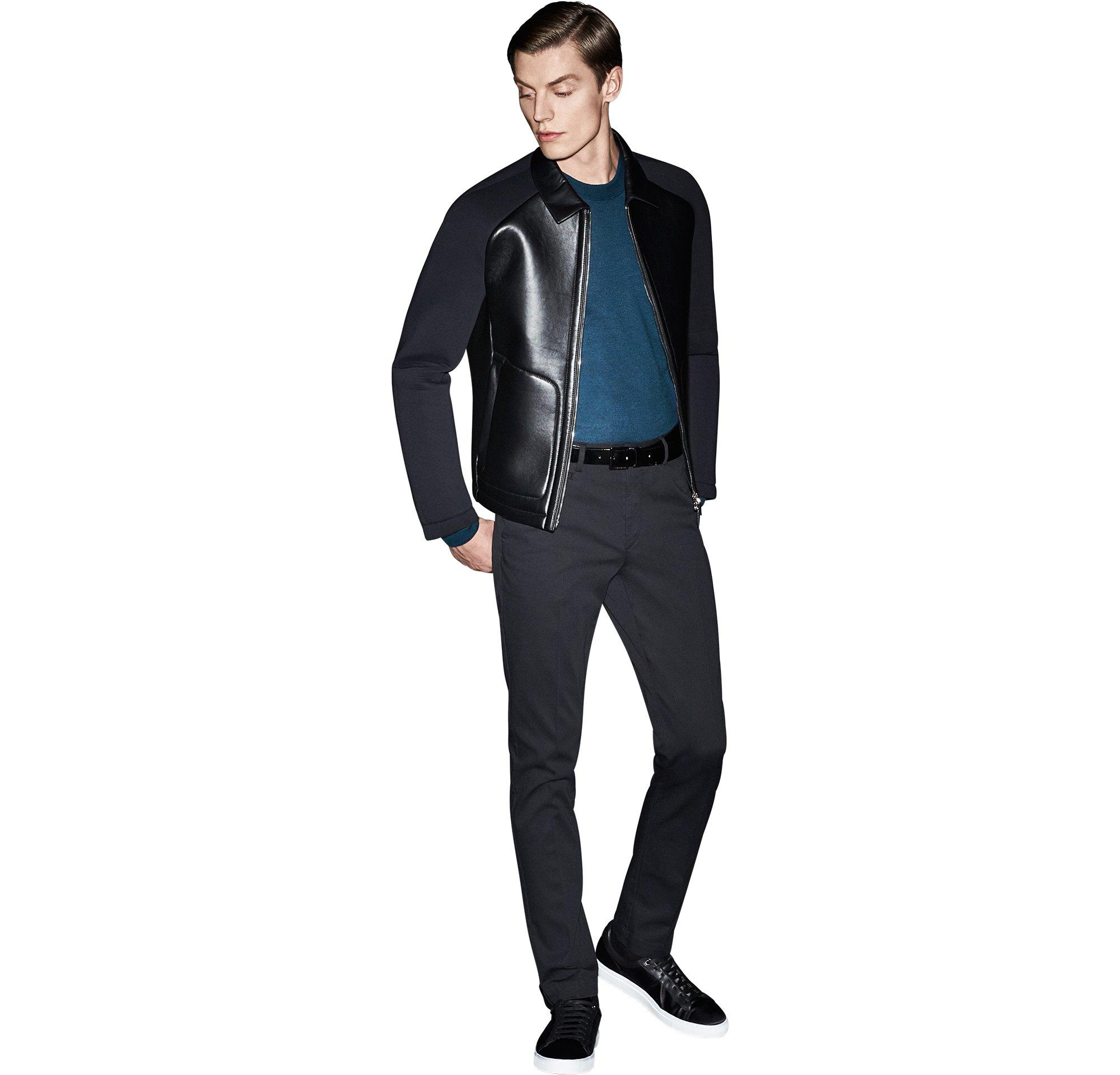 Schwarze Lederjacke über blauem Strickoberteil, schwarze Hose und schwarze Schuhe von BOSS