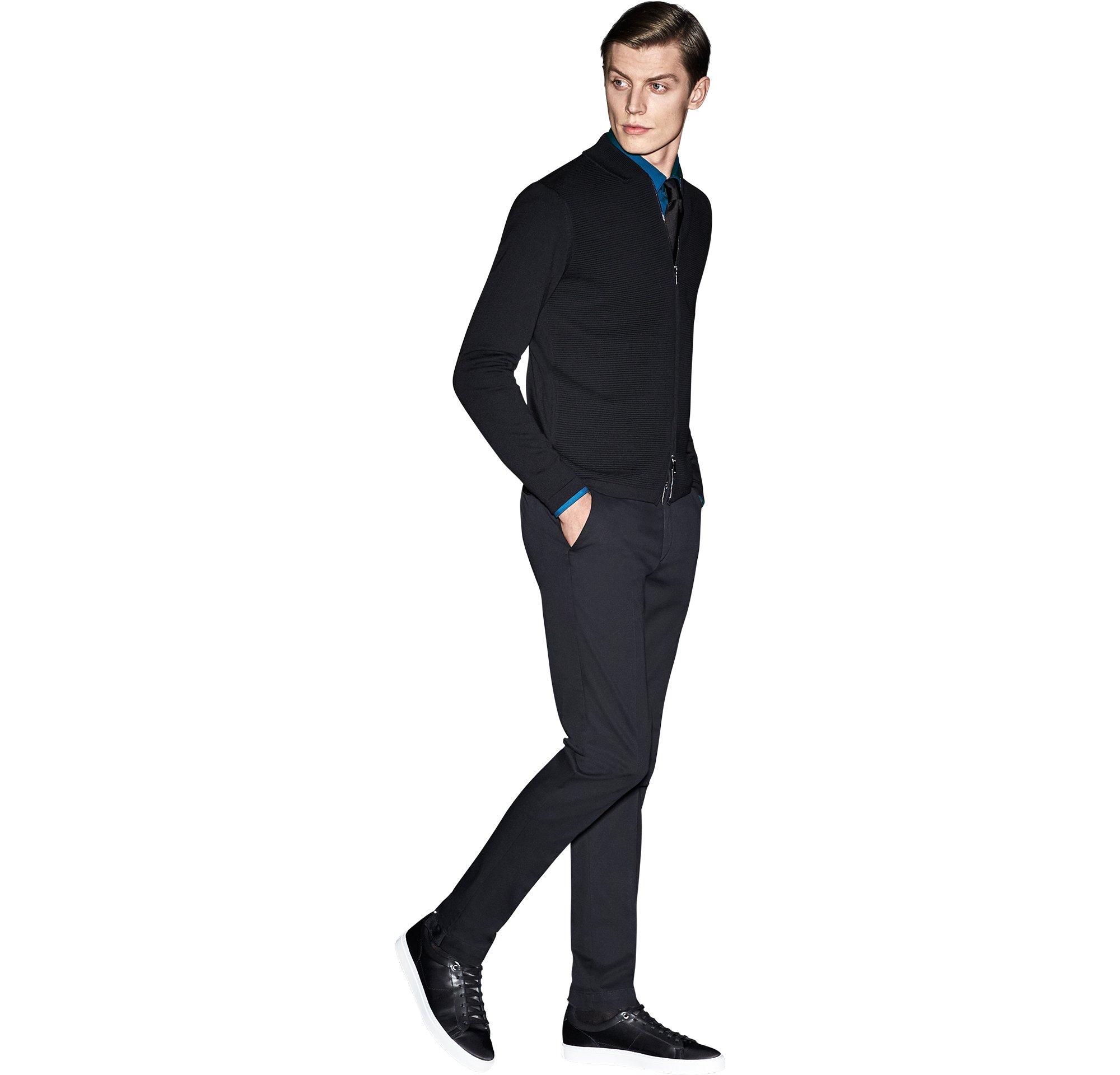 Schwarzes Strickoberteil über blauem Hemd, schwarze Hose und schwarze Schuhe von BOSS