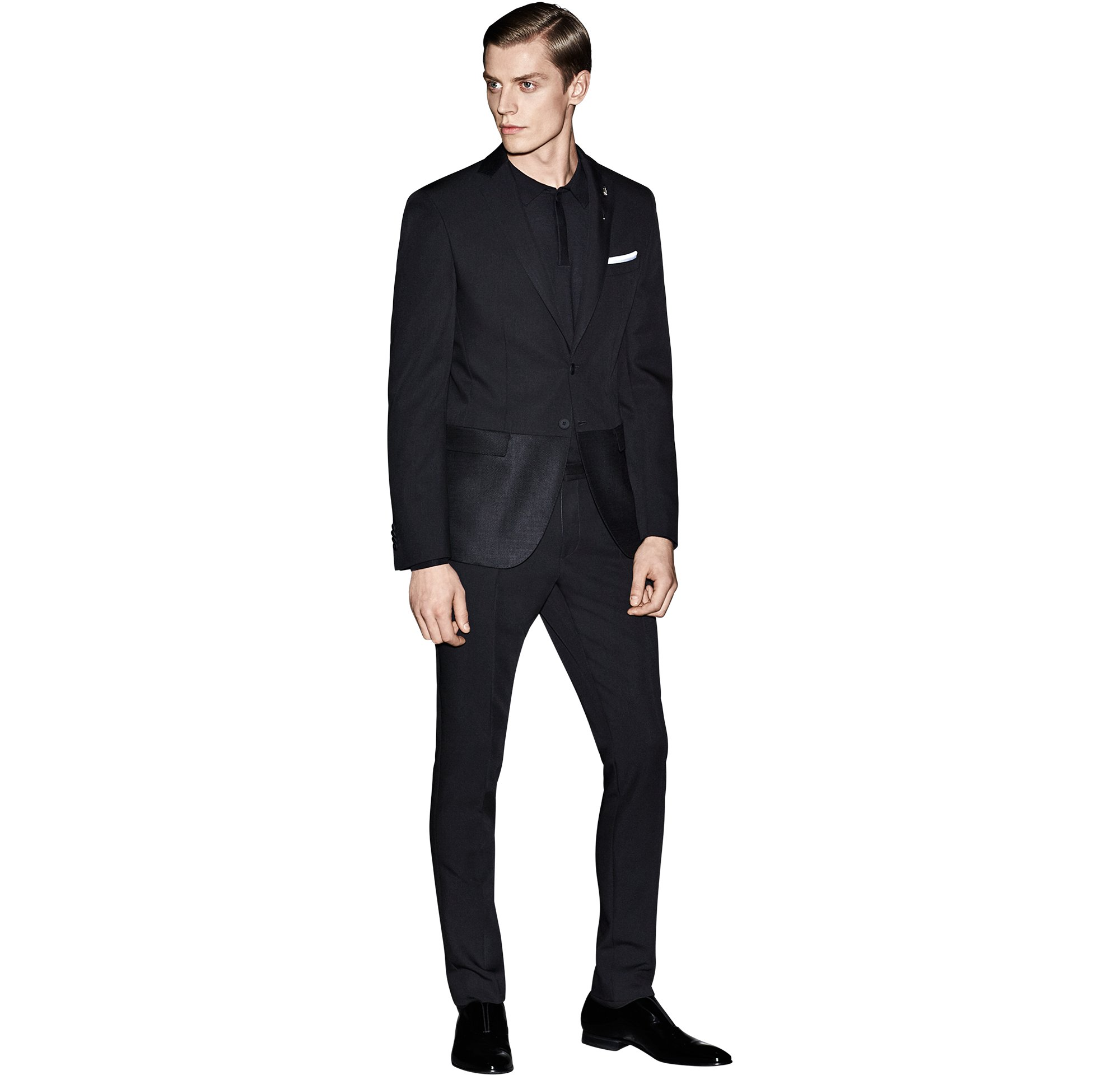 Schwarzes Sakko über schwarzem Strickoberteil, schwarze Hose und schwarze Schuhe von BOSS