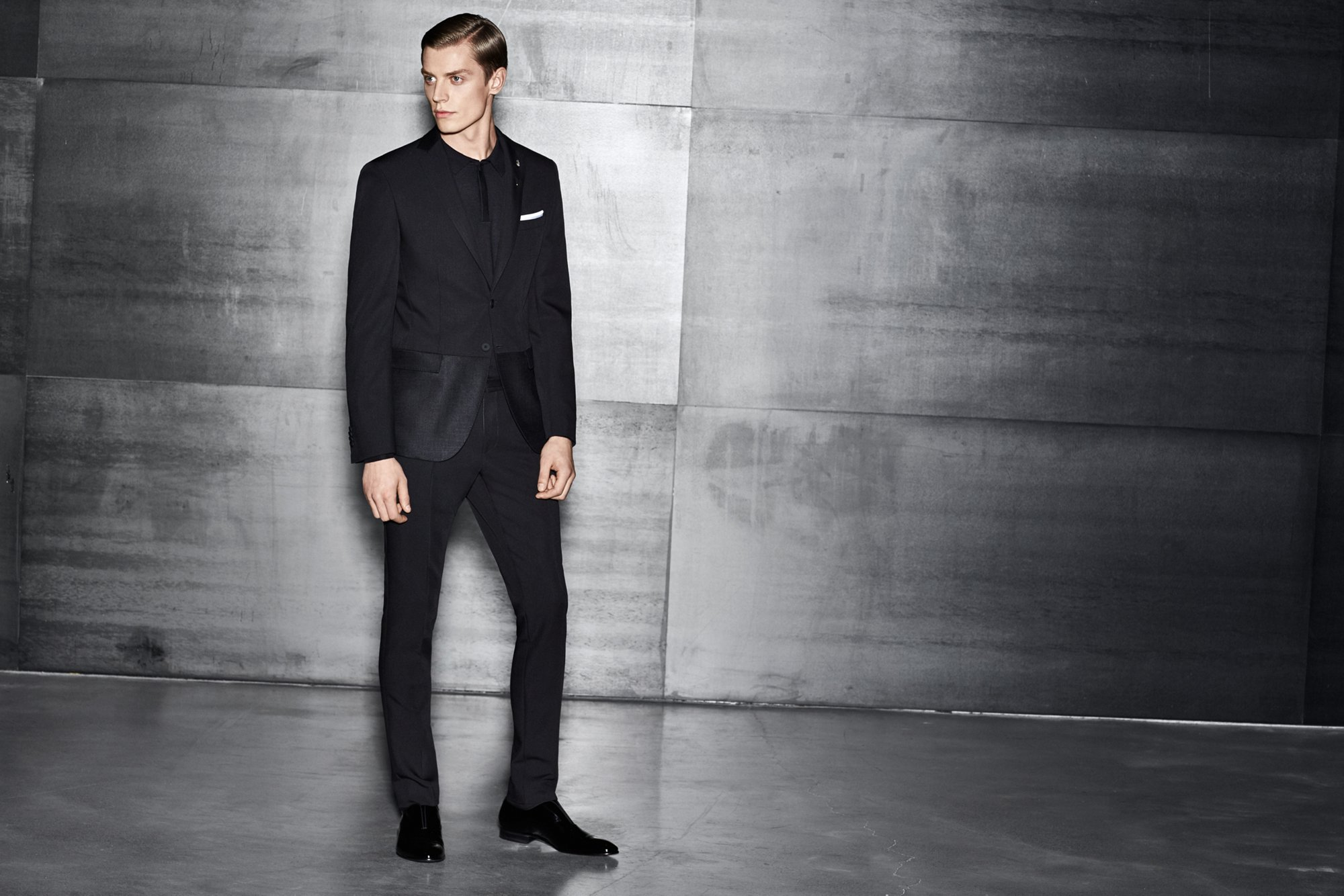 Black jacket over black knitwear and black trousers with black shoes by BOSS