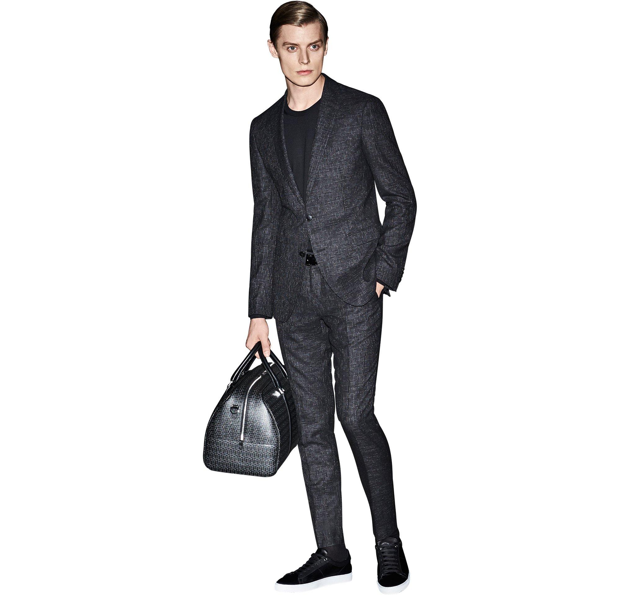 Schwarzer Anzug über schwarzem Strickoberteil, schwarze Ledertasche und schwarze Schuhe von BOSS