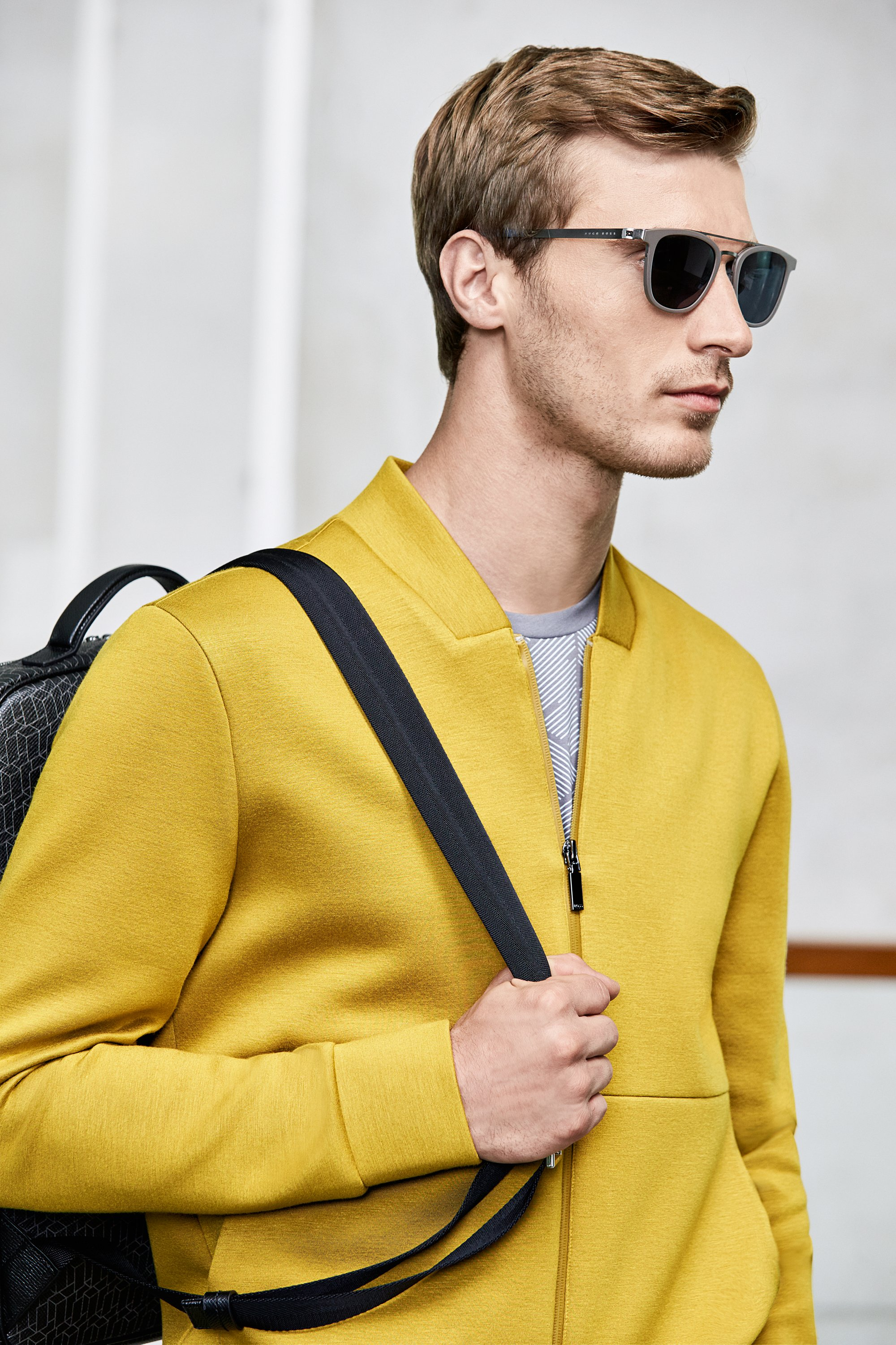 Grey suit over yellow knitwear and grey leather bag by BOSS