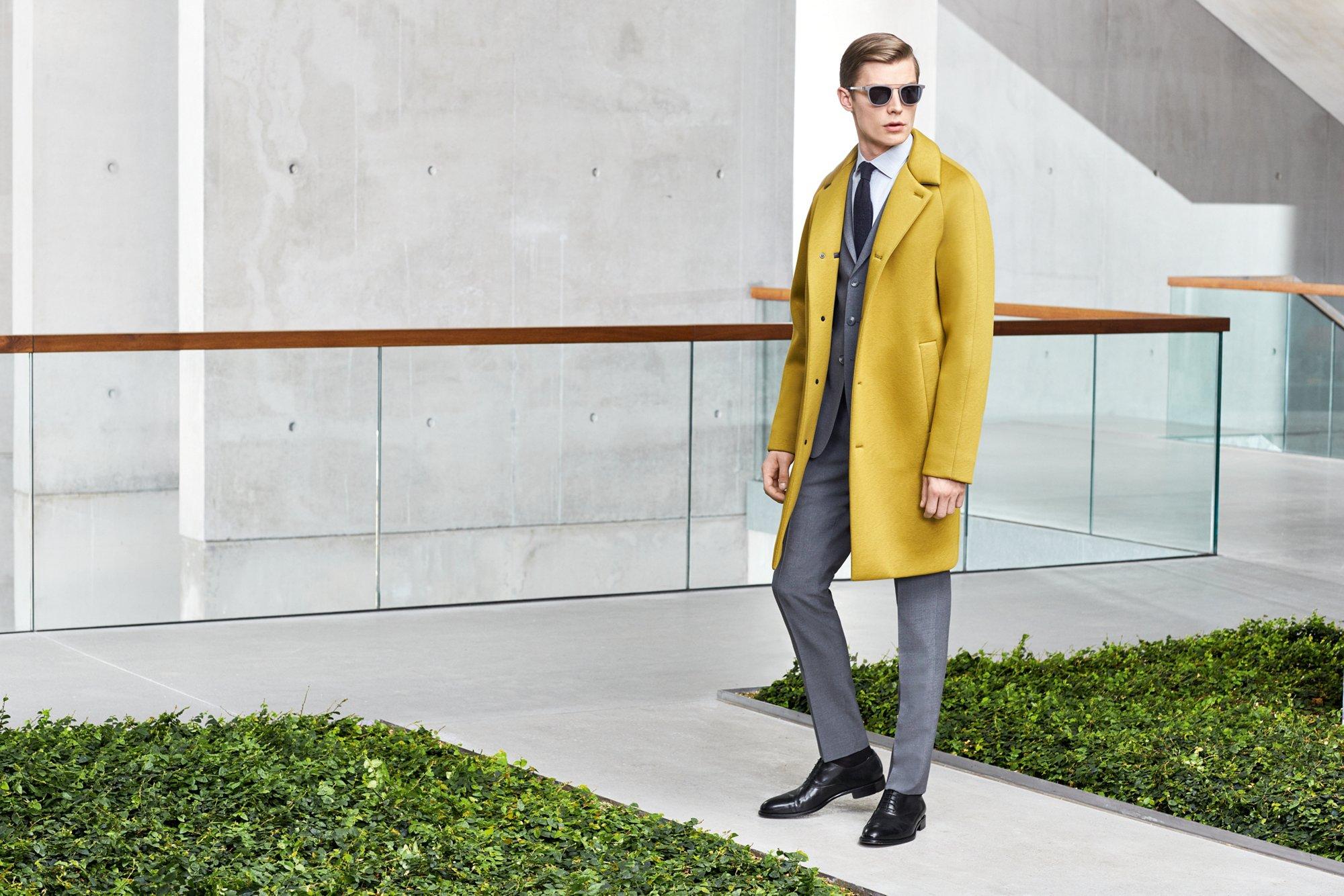 Manteau jaune au-dessus d'un costume gris avec une chemise blanche et des chaussures noires BOSS