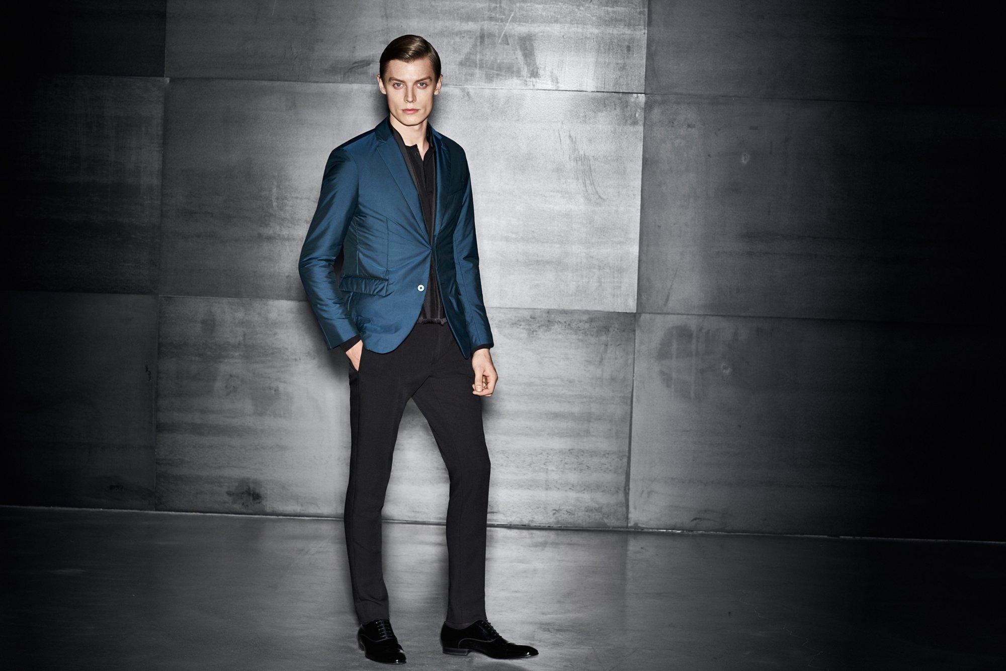 Blaues Sakko über schwarzem Strickoberteil, schwarze Hose und schwarze Schuhe von BOSS