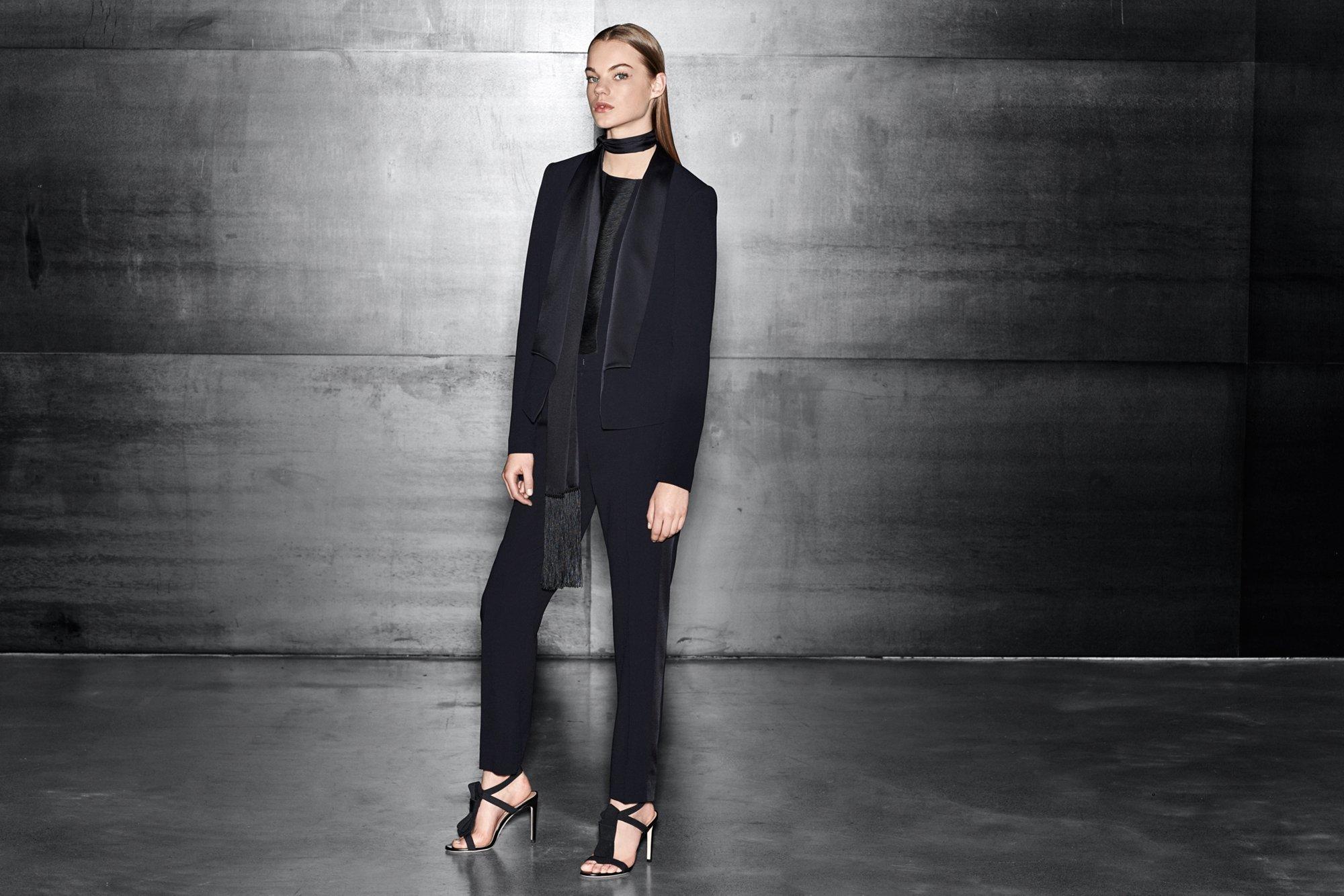 Schwarze Jacke über schwarzer Bluse, schwarze Hose und schwarze Schuhe von BOSS