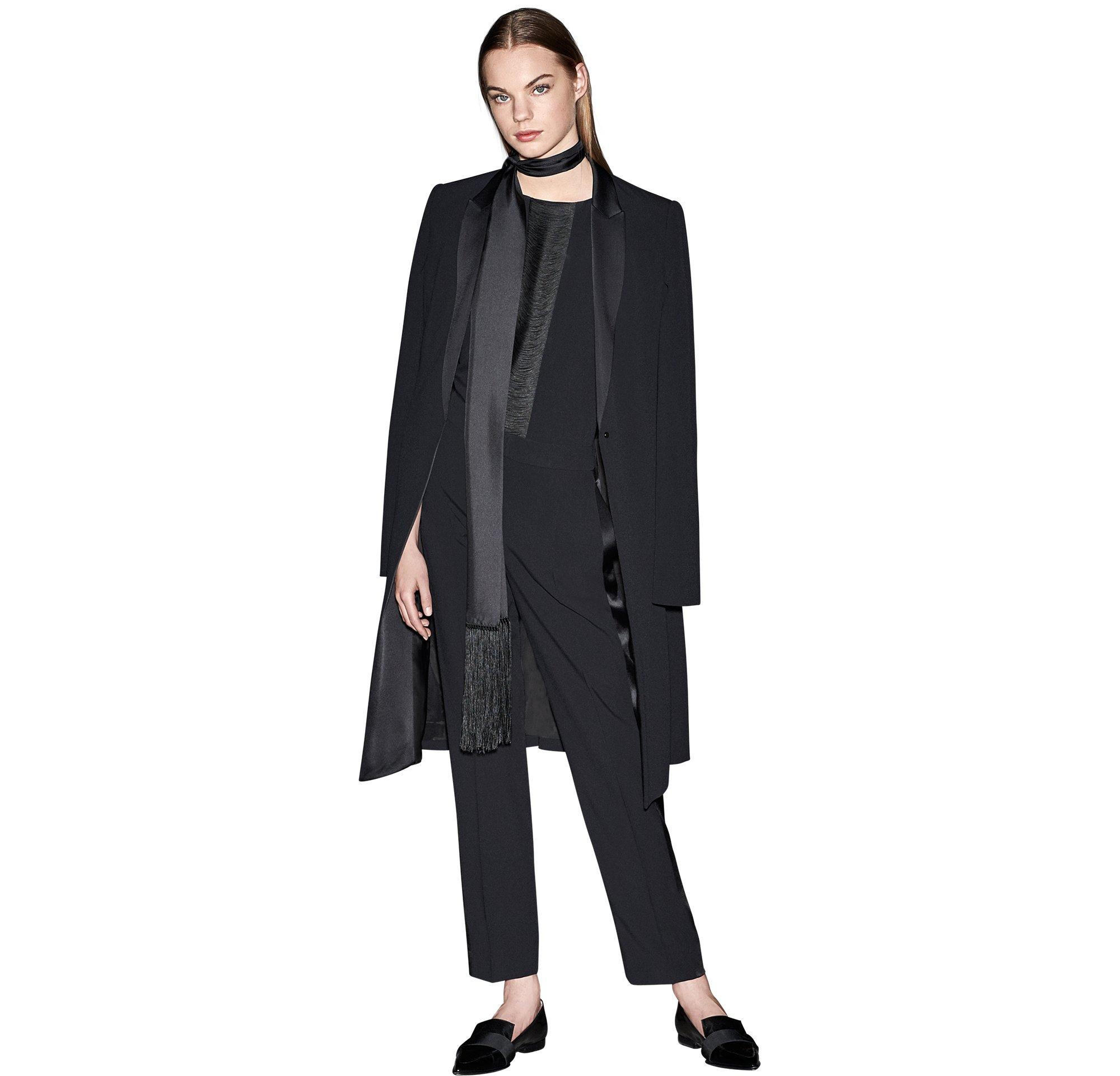 Schwarzer Mantel über schwarzem Top, schwarze Hose, schwarzer Schal und schwarze Schuhe von BOSS
