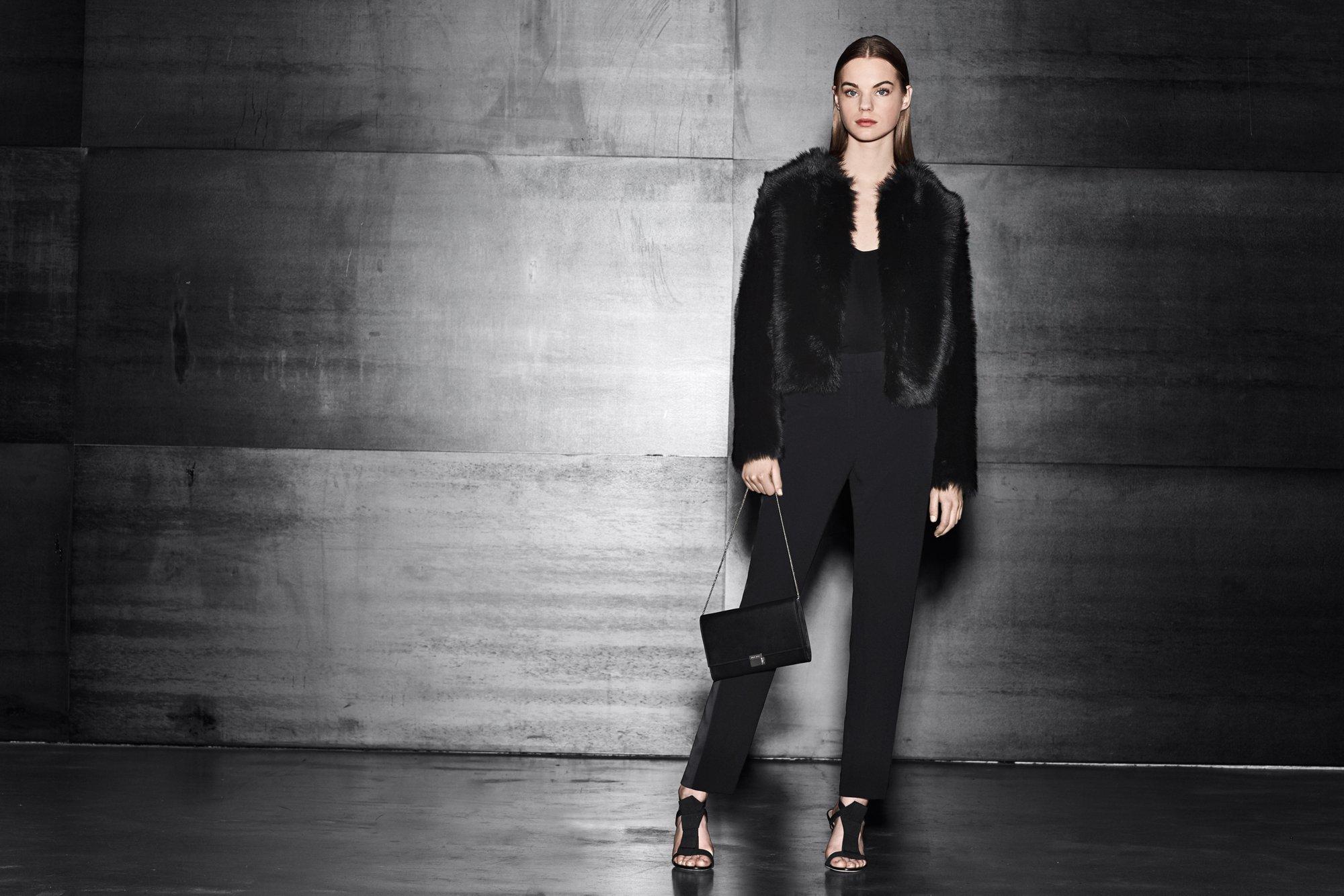 Schwarze Lederjacke über schwarzem Top, schwarze Hose, schwarze Tasche und schwarze Schuhe von BOSS