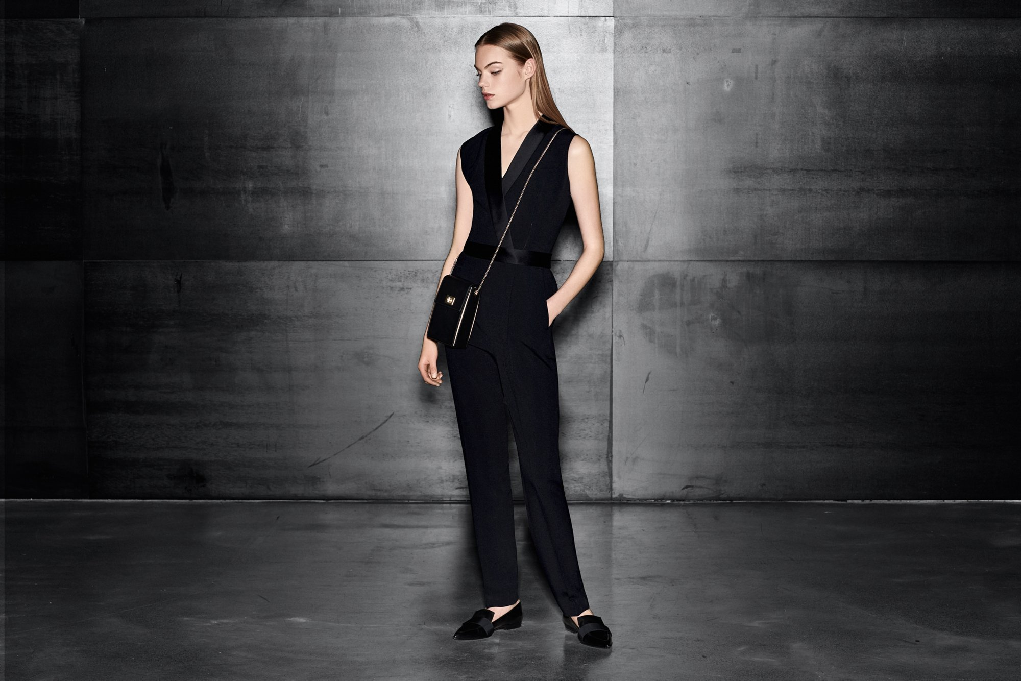 Black jumpsuit with a black bag and black shoes by BOSS