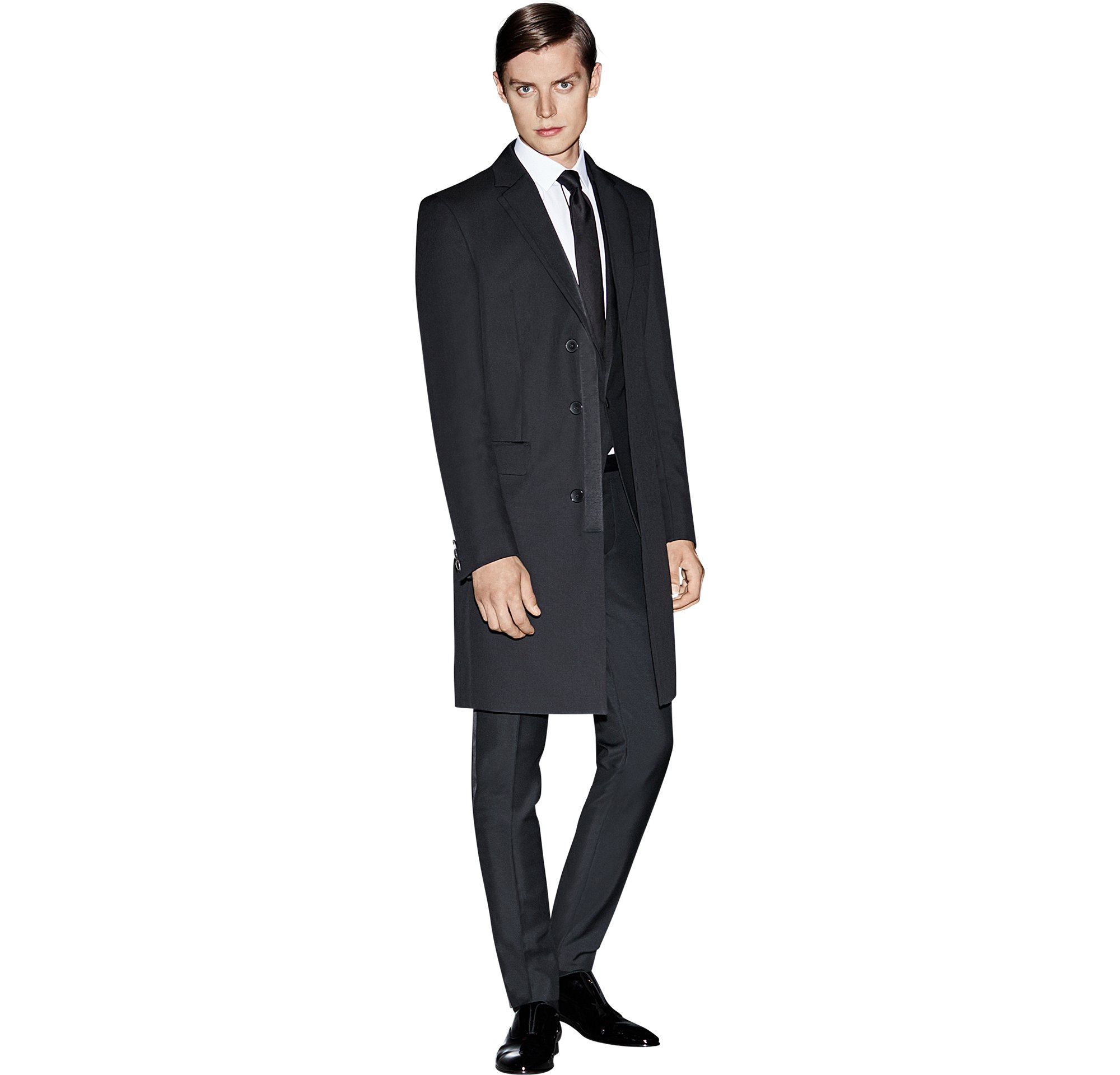 Schwarzer Mantel über schwarzem Anzug, weißes Hemd mit schwarzer Krawatte und schwarze Schuhe von BOSS