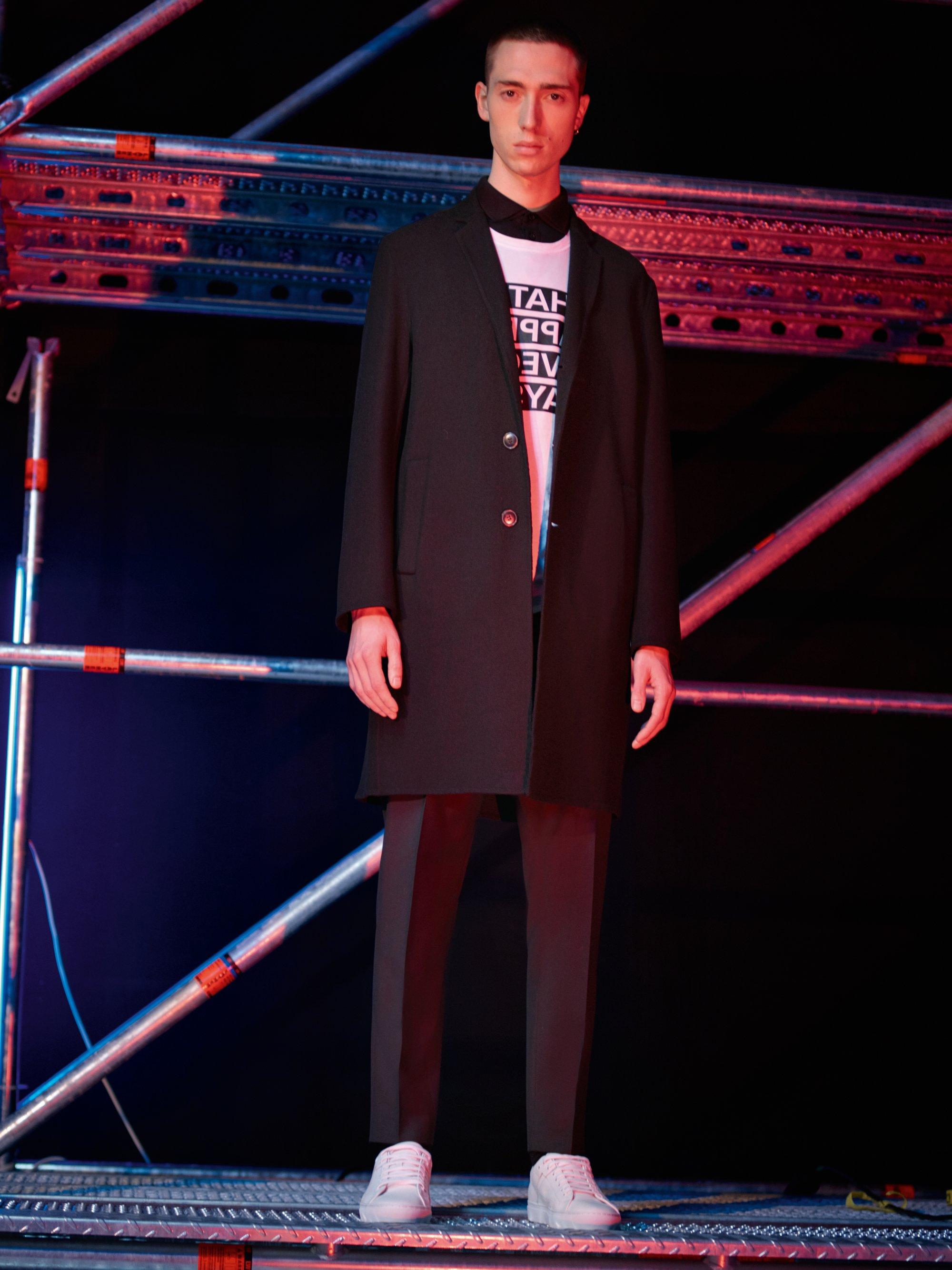 Schwarzer Mantel über weißem Jersey, schwarze Hose und weiße Schuhe von HUGO