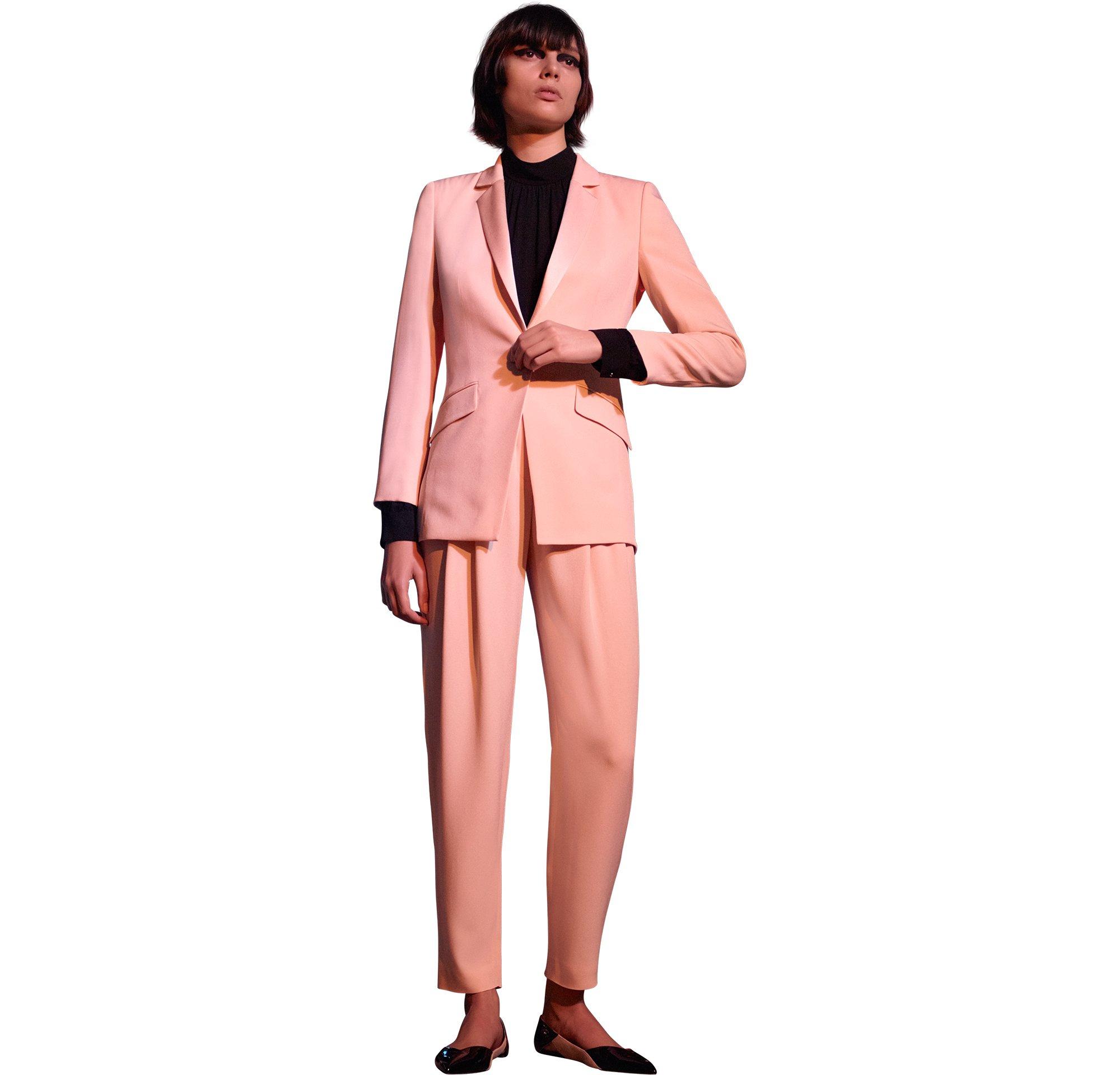 Rosa Jacke über schwarzem Top, rosa Hose und schwarze Schuhe von HUGO