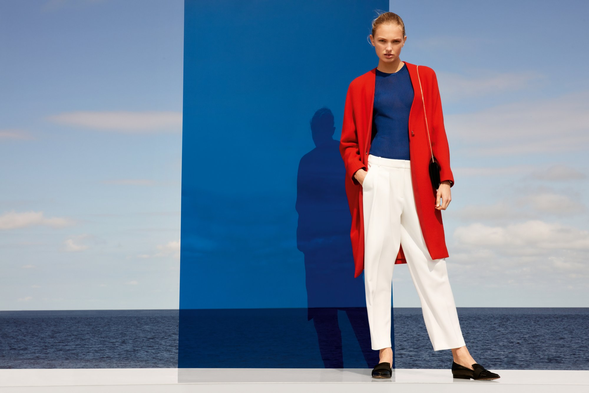 red coat over blue knitwear and white trousers with black bag by BOSS