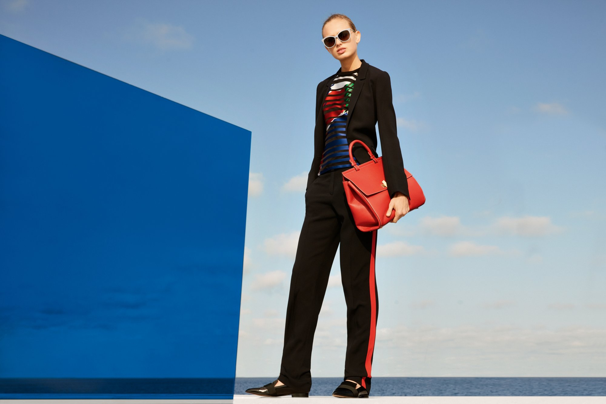 black casual trousers with a black blazer and the red BOSS Bespoke Soft Bag