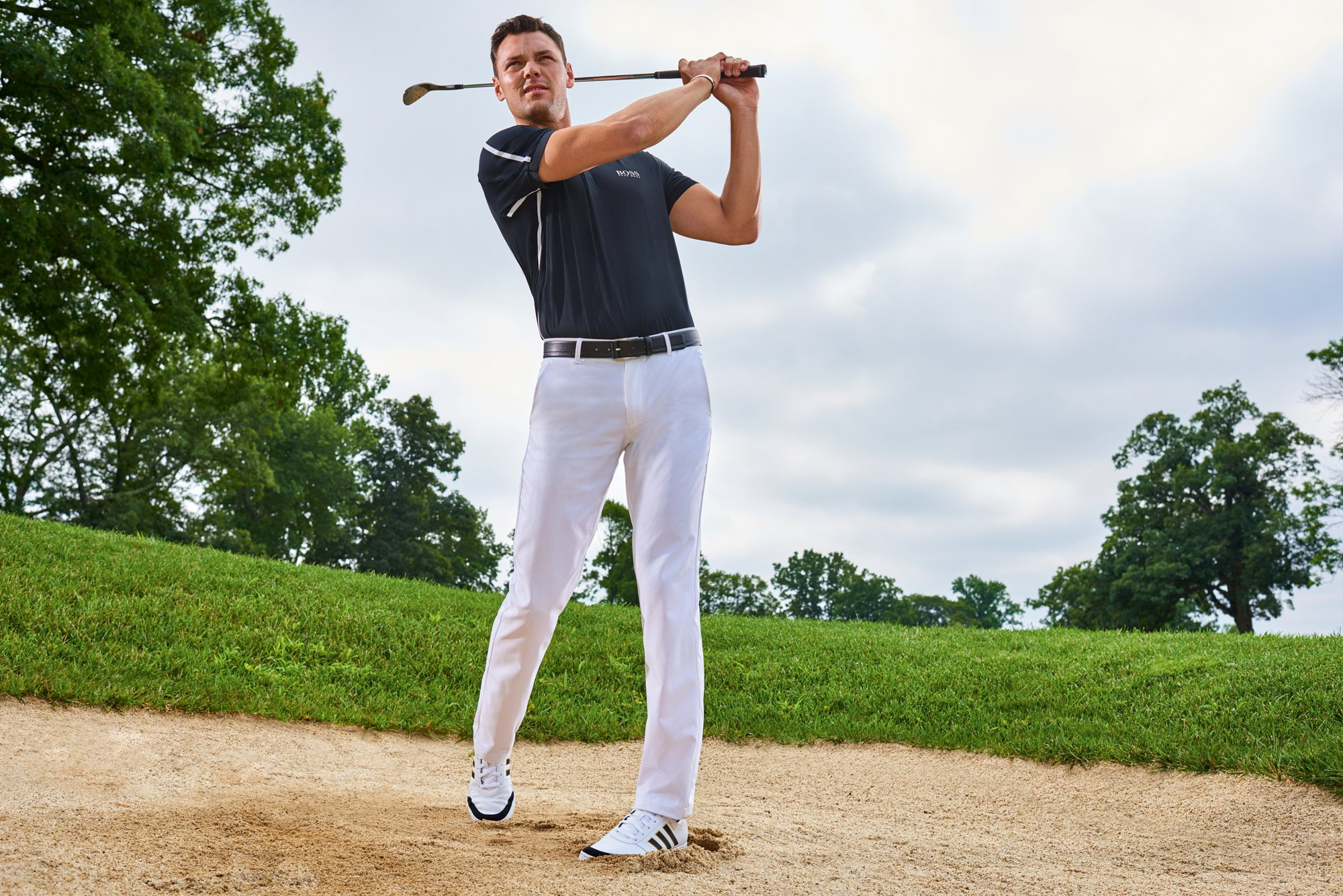 Martin Kaymer is wearing white trousers and a black polo from BOSS Green