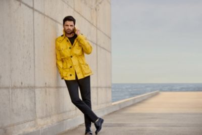 Sebastian Stan wearing yellow rain coat from Boss Menswear