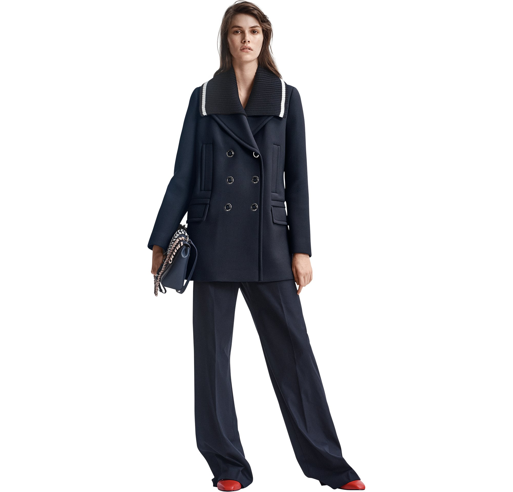 Dame mit blauer Jacke, blauer Hose und roten Schuhen von BOSS Womenswear