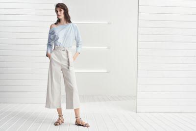 Le mannequin porte un chemisier à épaules dénudées boutonnées avec un pantalon léger